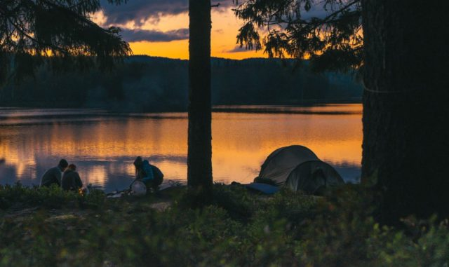 Group of campers making a fire beside their tent along a lake.
