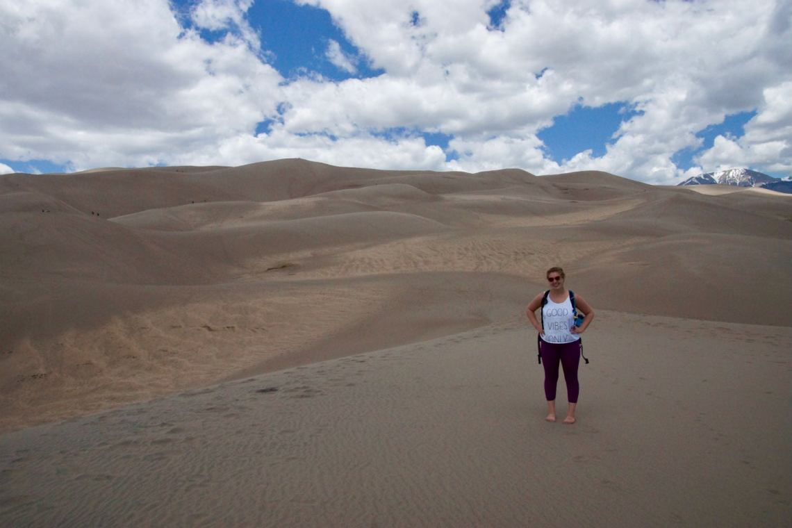kelsey and sand dunes on her budget camping trip