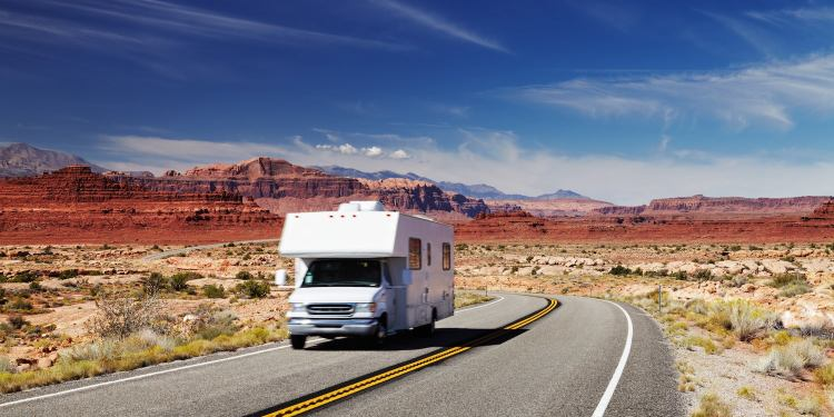 rv traveling down desert road