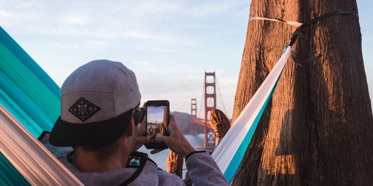 man lounges in hammock while photographing golden gate bridge in background