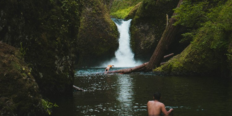 two people swim in a natural pool near a short cascading oregon waterfall