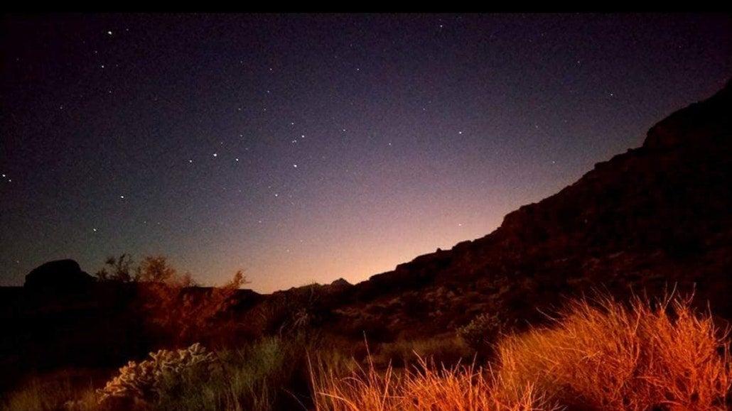 the starry night sky over a grassy desert in california