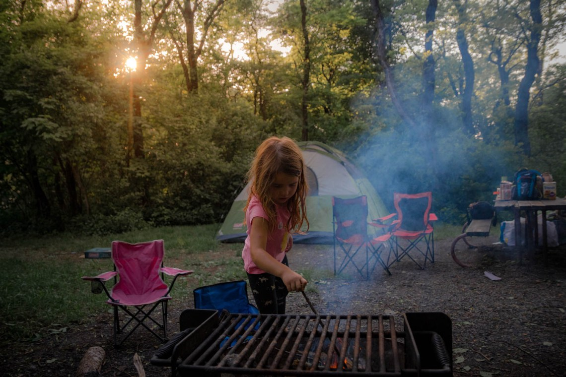 sun shines between the trees as young girl pokes at campfire
