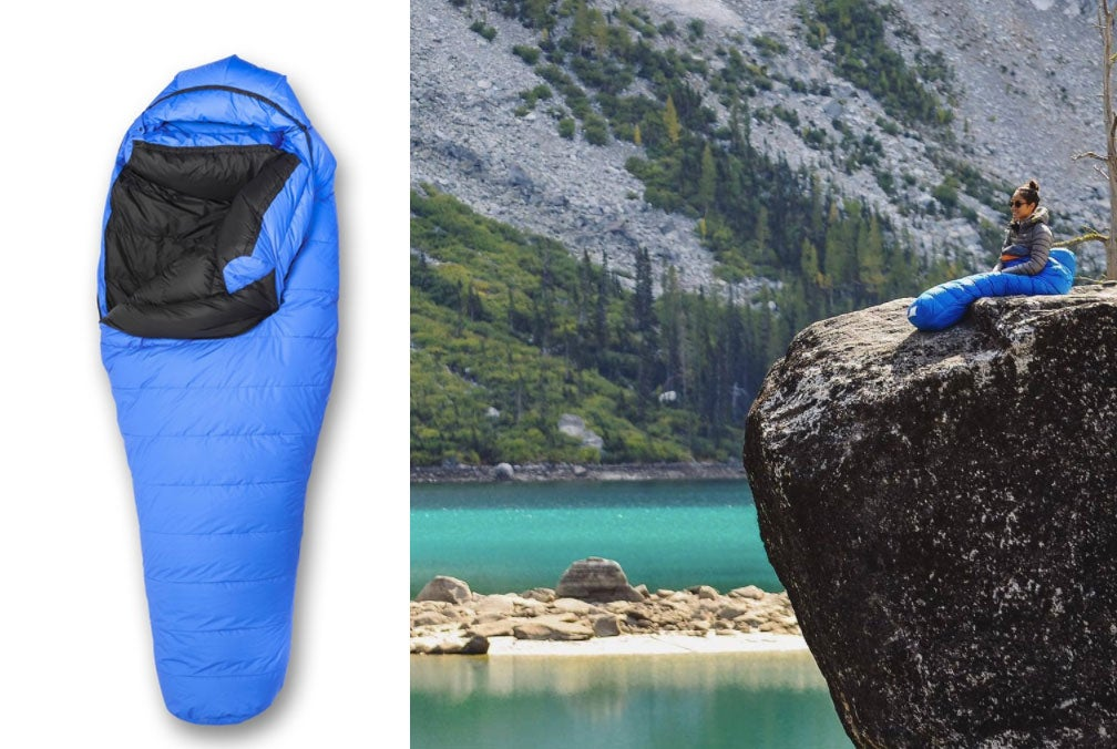 wide shot of women resting on cliff beside glacial water in her blue sleeping bag