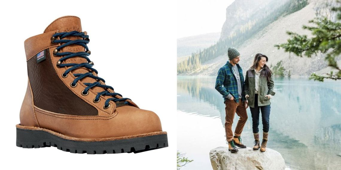 couple poses on a lakeside rock in their brown leather hiking boots