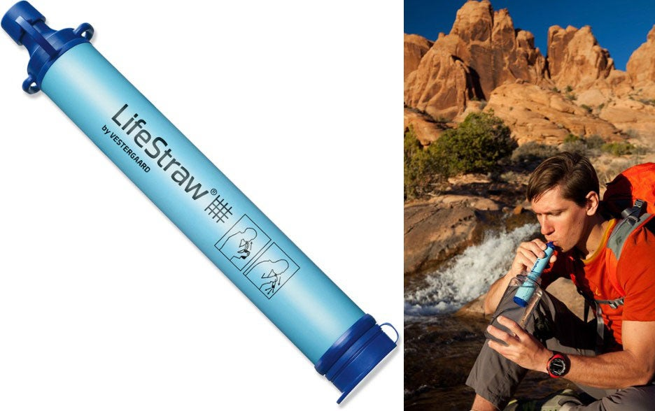 man uses lifestraw in stream beside red rocks