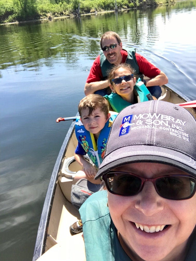 family of kayakers pose for selfie from their kayak on the water at lake metigosh state park