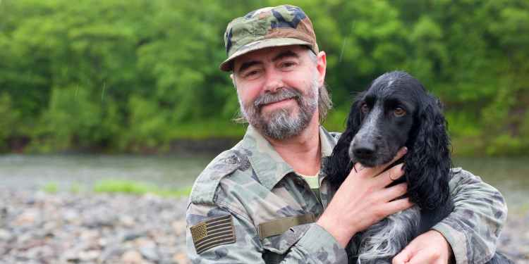 veteran on river bank with dog help veterans heal via wilderness therapy programs