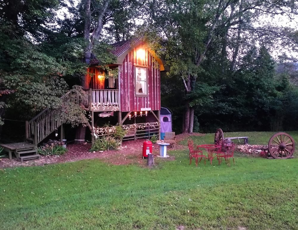 weathered red treehouse illuminated over a furnished lawn