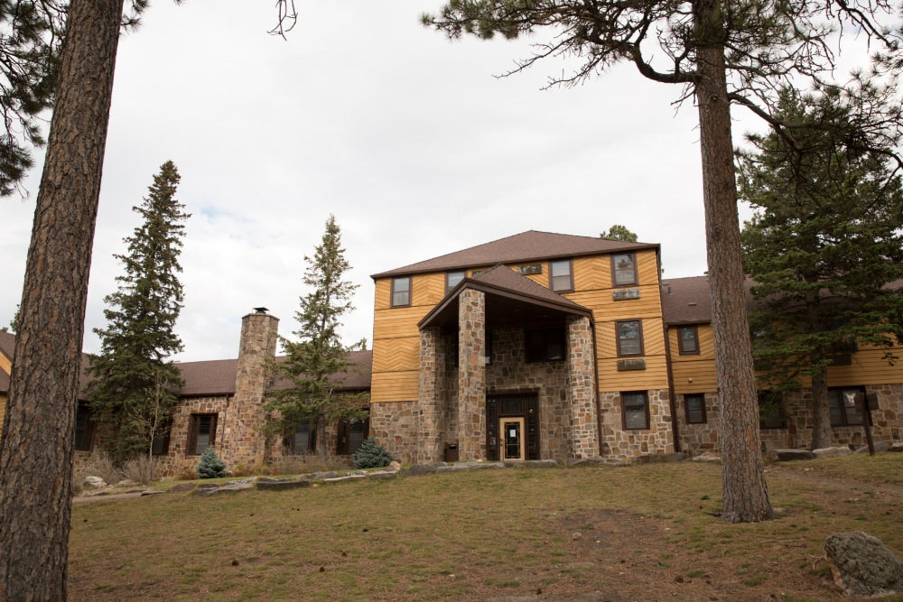 stone entrance to sylvan lake lodge from the surrounding trees