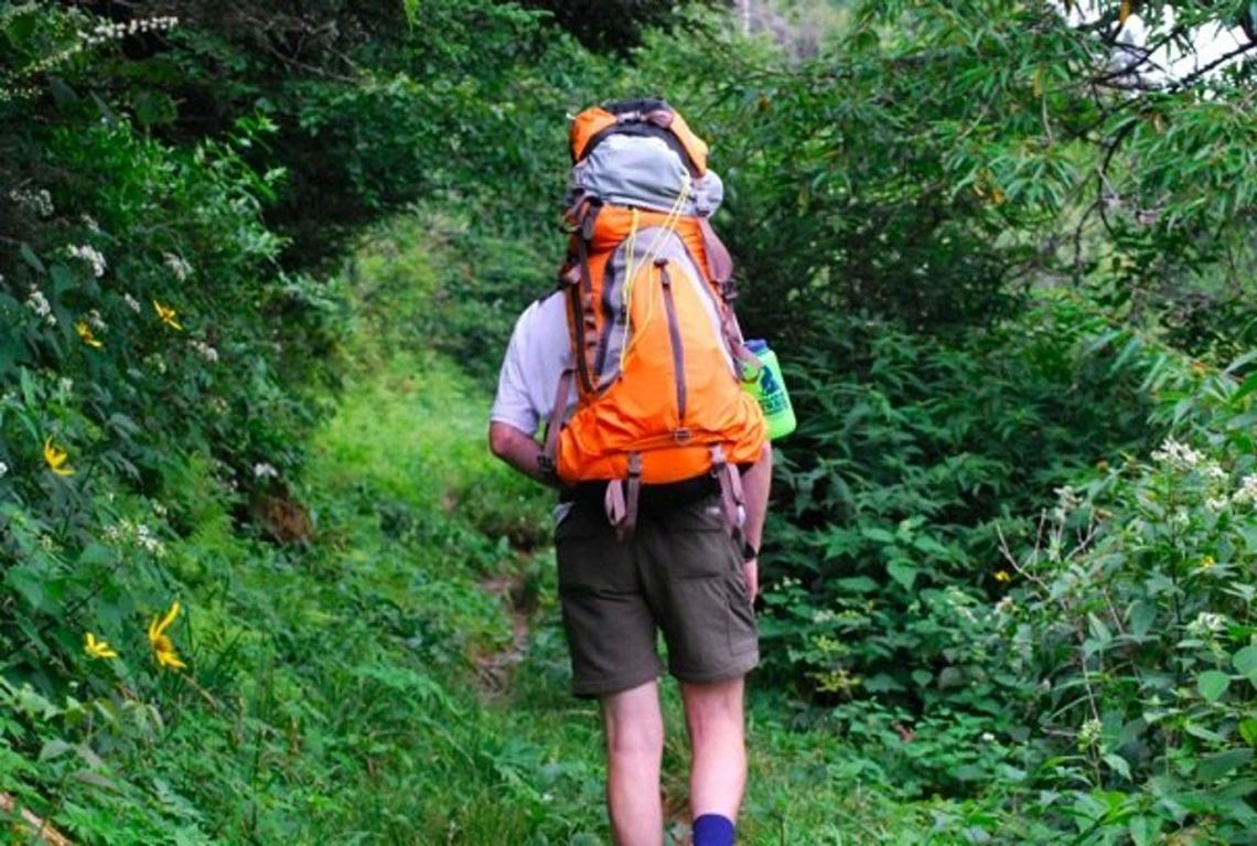 hiker carrying an orange backpack up to the mount le conte shelter