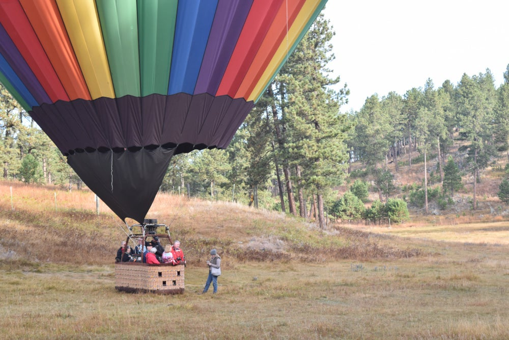 Wide angle shot of a hot air balloon with several people inside the basket ready for a hot air balloon ride