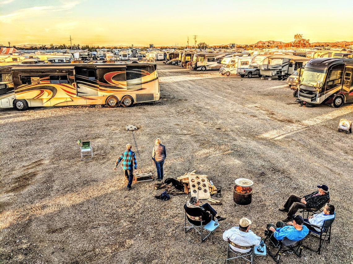 campers play a game on an open field in Quartzsite, AZ near a large field of campervans and RV trailers