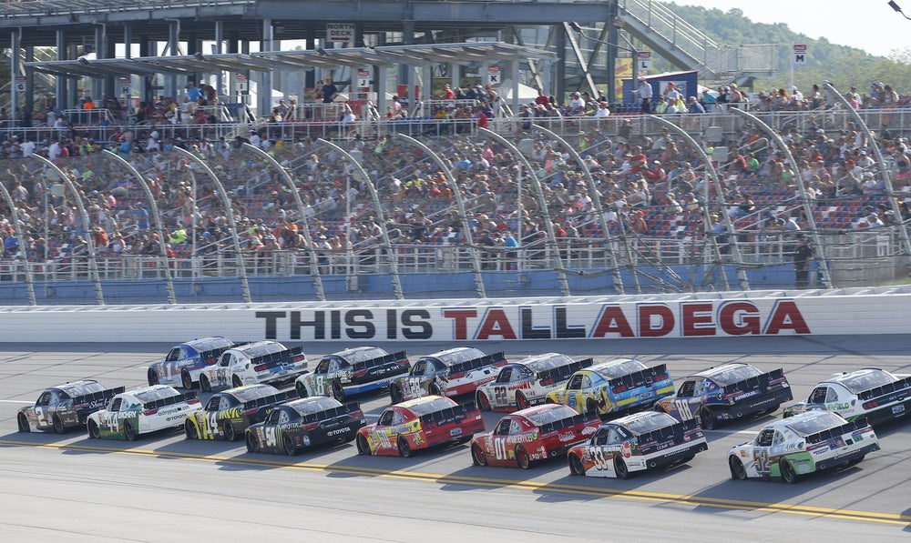 """Multiple cars close together racing on NASCAR home track in Alabama. Sign on track says """"This is Talladega"""""""