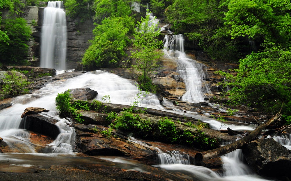 Wide angle photo of the Twin Falls waterfalls in SC flowing over rocks and greenery
