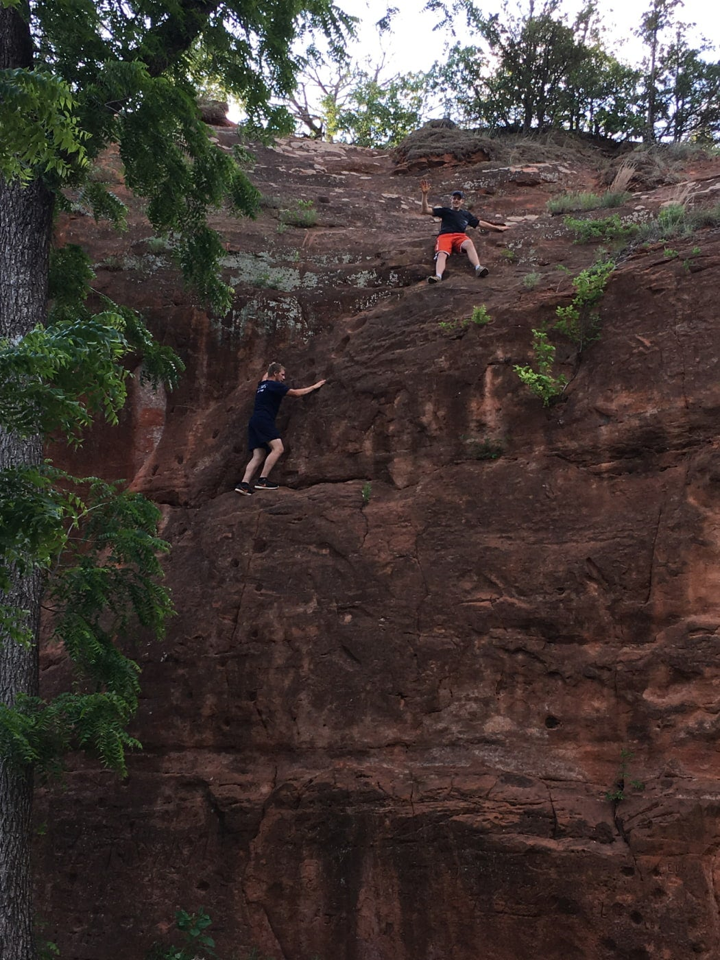 two men bouldering on natural rock wall in an oklahoma state park