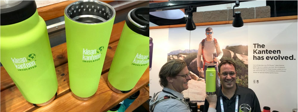 three klean kanteen insulated water bottles stand in a line, one with out a top, and a man holds a water bottle near the head of another man at a convention booth
