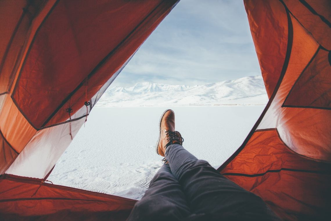 view from inside of tent showing a camper stretching his legs out of the door into a field of fresh snow