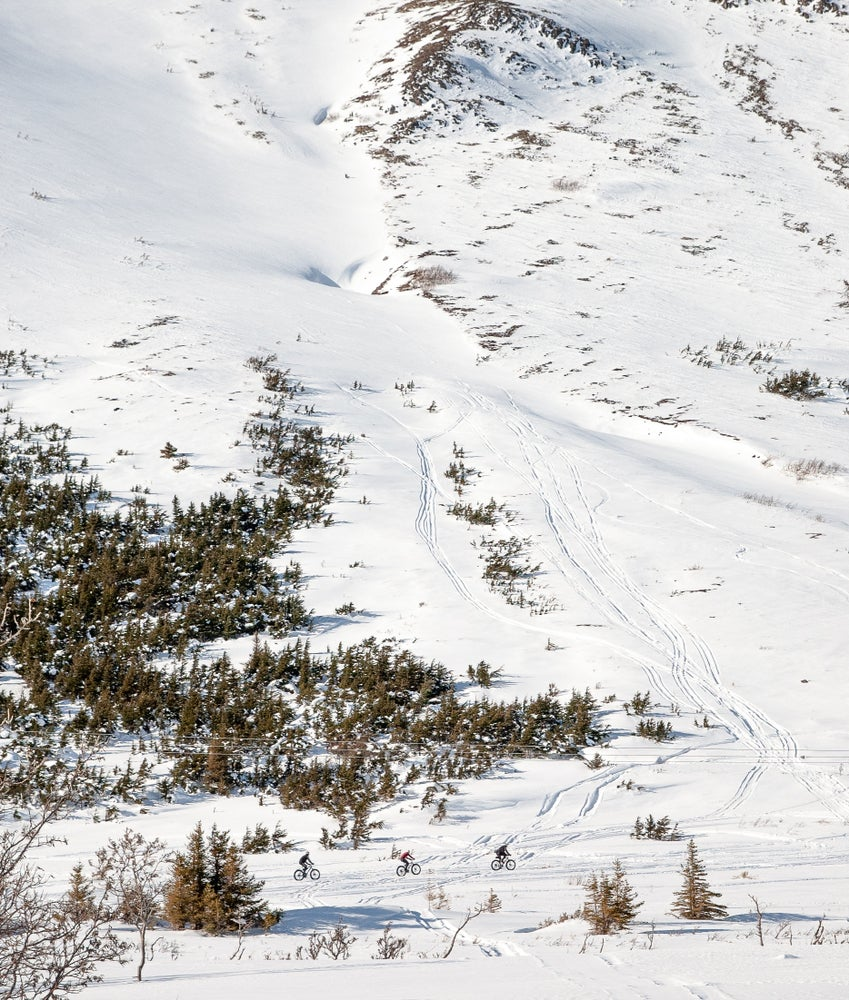 Fat bike trails visible from aerial view of snowy mountainside in Chugach, Alaska
