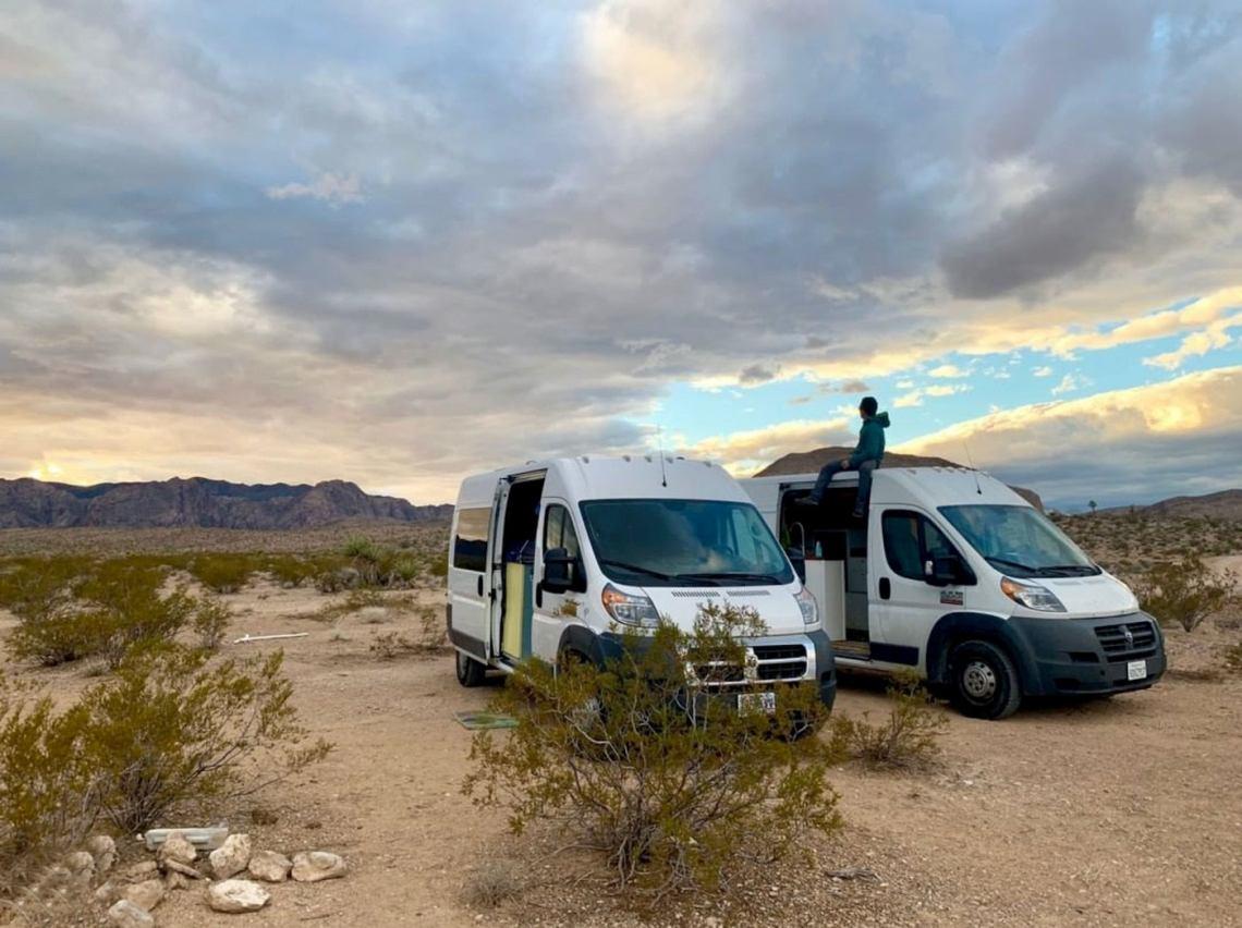 Man sitting on a sprinter van beside another sprinter in the desert.