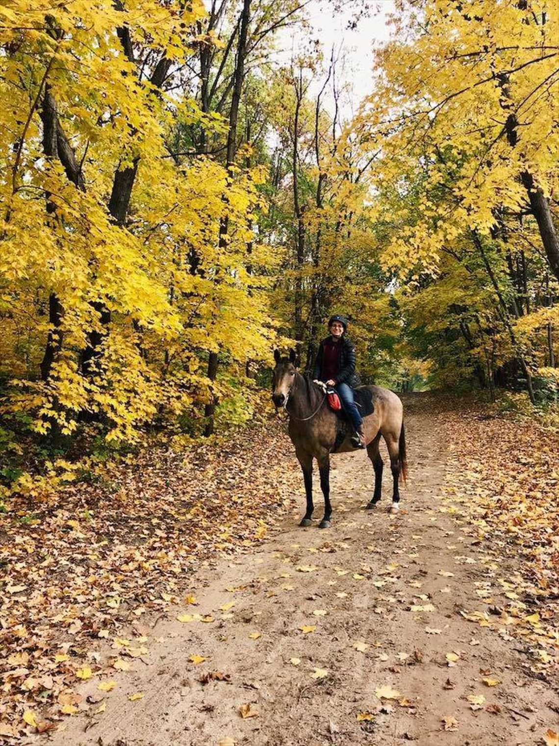 Women poses on horseback in the woods beneath yellow autumn foliage.