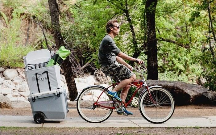 a RovR cooler attached to a bike ridden by a man
