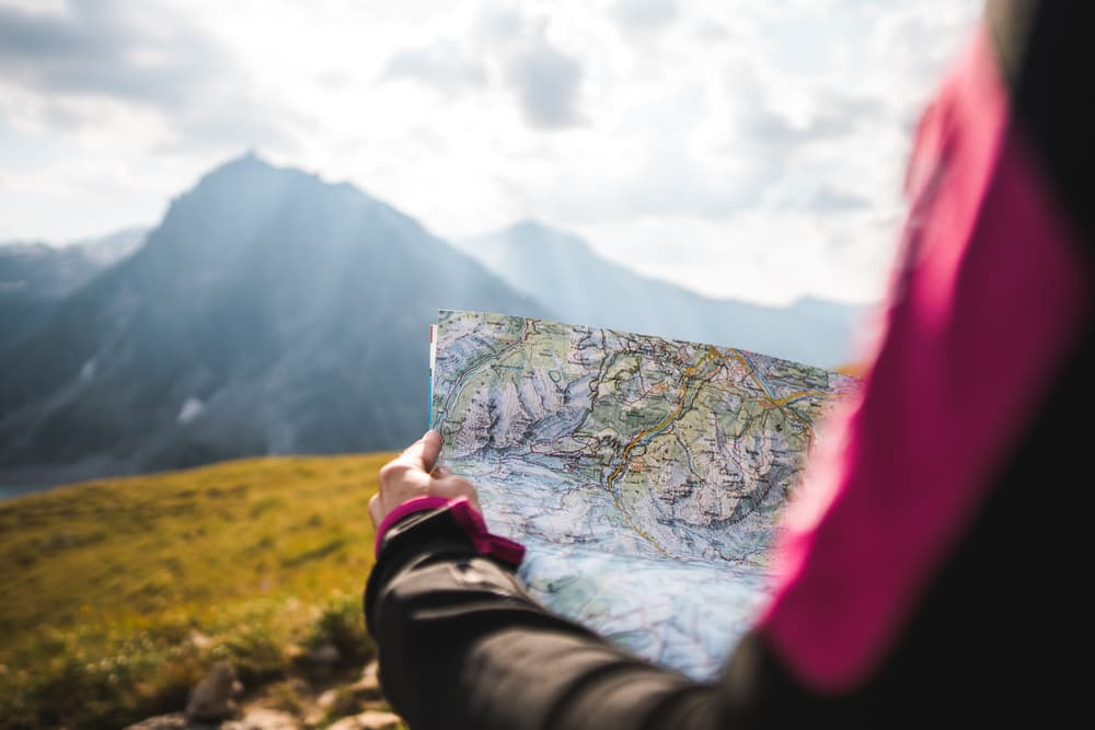 woman holding topographical map overlooking mountains