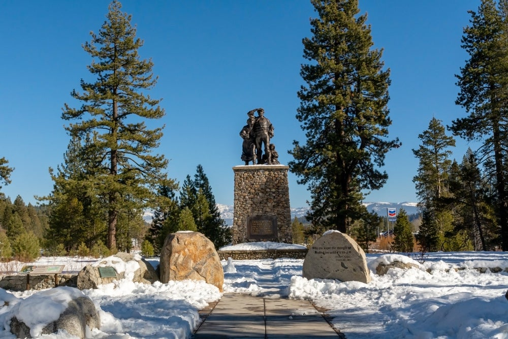 snow covers the ground in front of a metal statue at the Donner Memorial State Park and Emigrant Trail Museum