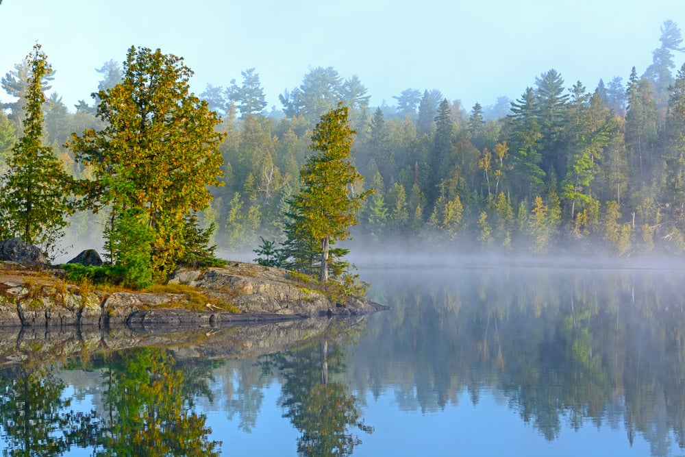 a wide angle view of fog over lake in minnesota with trees and stone on island