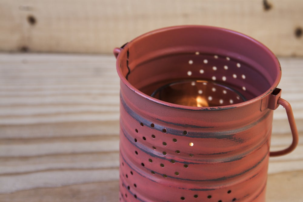 Tin can with candle inside sitting on a table