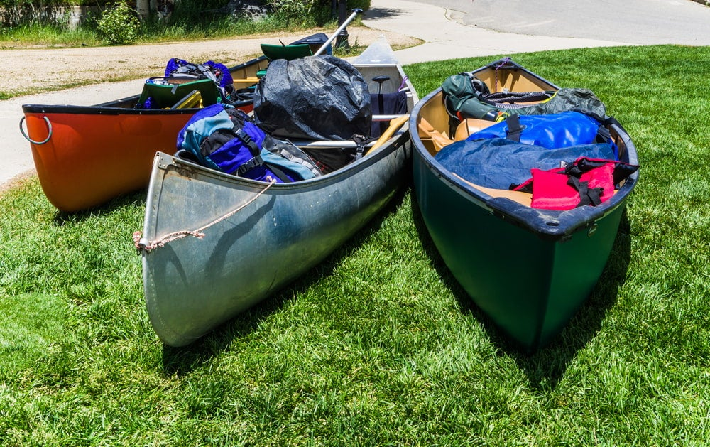 Canoes packed full of gear on grass.