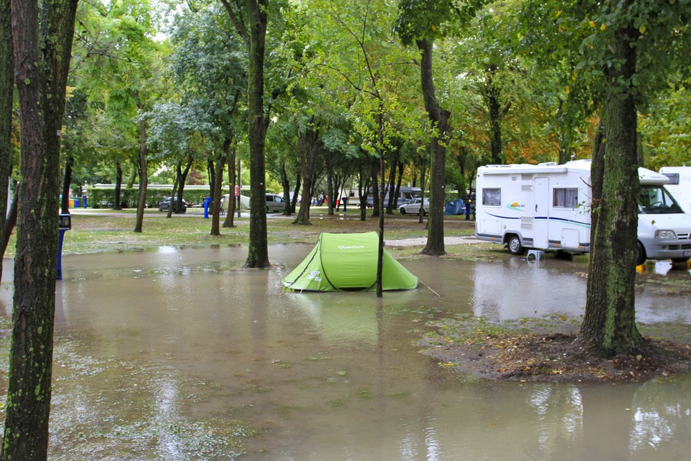 Green tent set up in the middle of a flooded campsite beside an RV