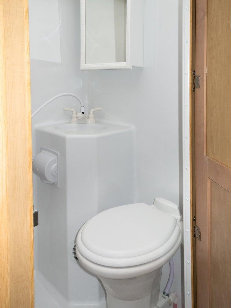 Traditional plastic rv toilet in a white plastic bathroom.