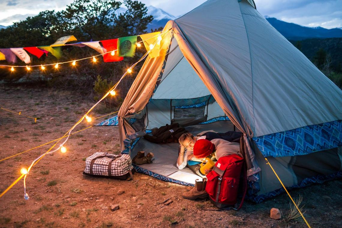 Campsite with Wenzel tent and string lights.