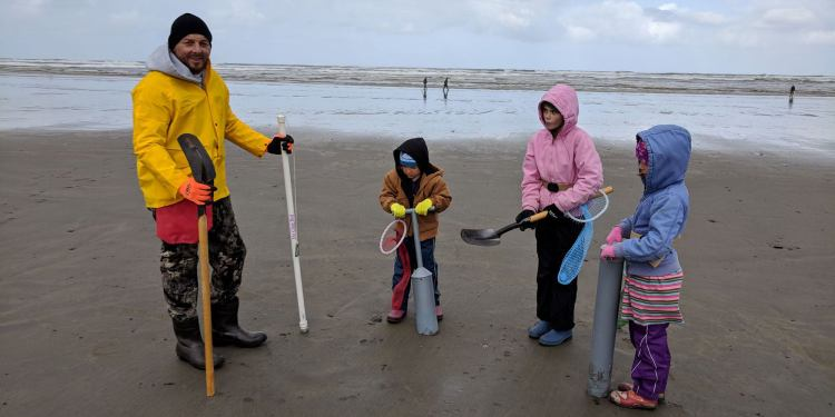 a family holding shovels wearing rain gear go digging for clams