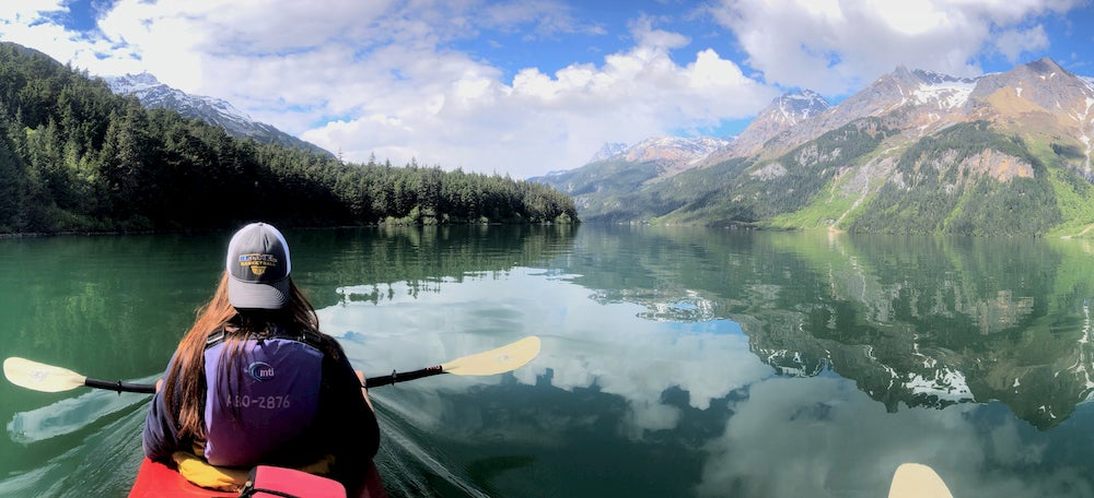 Woman kayaking in lake with large mountain on and trees in far distance