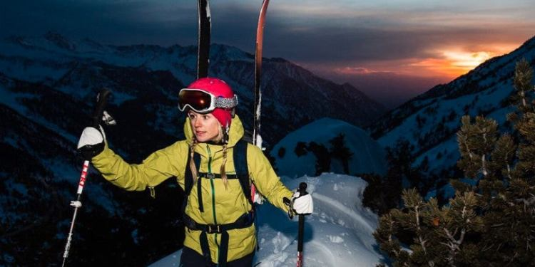 climber caroline gleich holding trekking ples in winter gear climbing a mountain at dawn