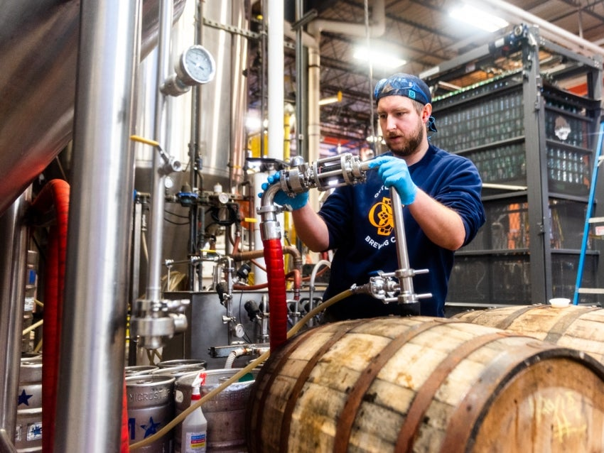 Man brewing beer with barrels in front of him
