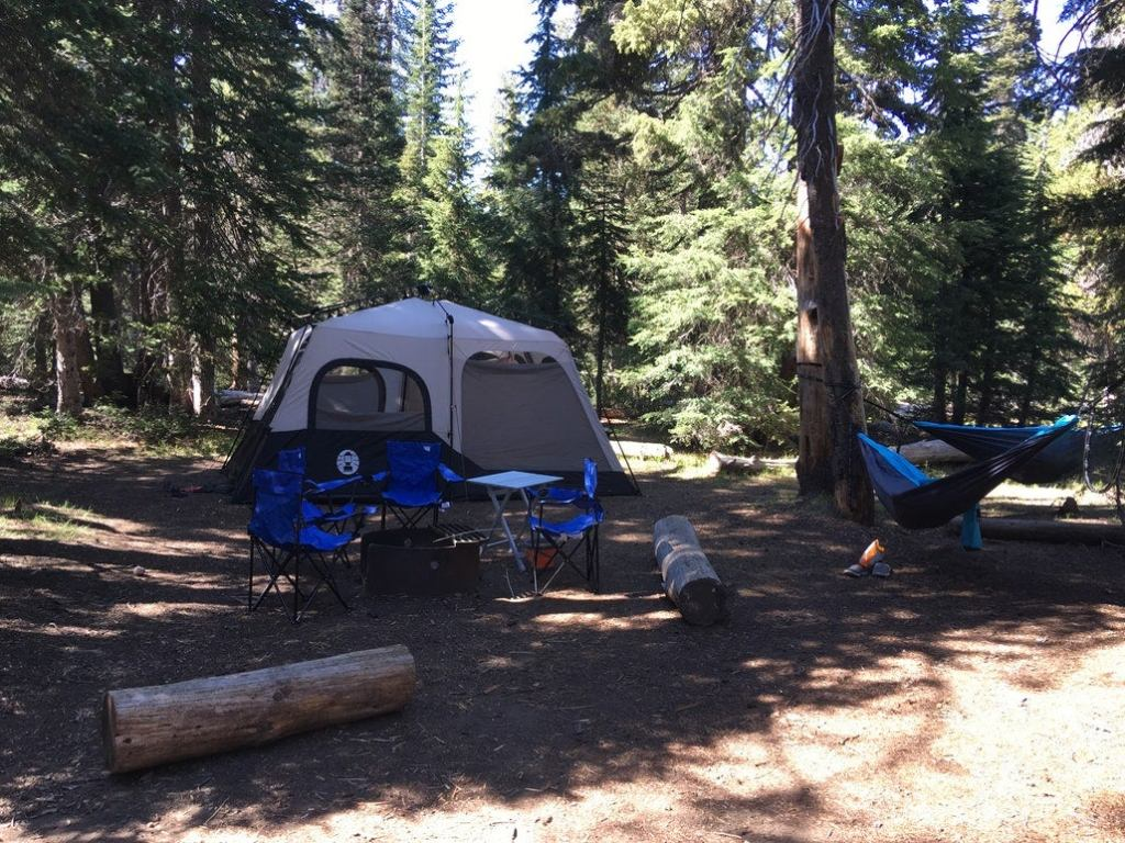 a fully assembled campground with a tent, camping table and fire pit in crater lake national park