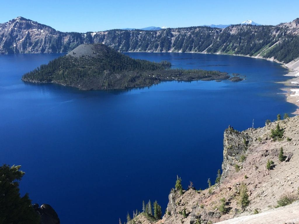 a photo of wizard island shooting out from the middle of crater lake in oregon