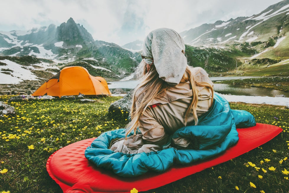 Woman lounged in sleeping bag surrounded by alpine landscape.