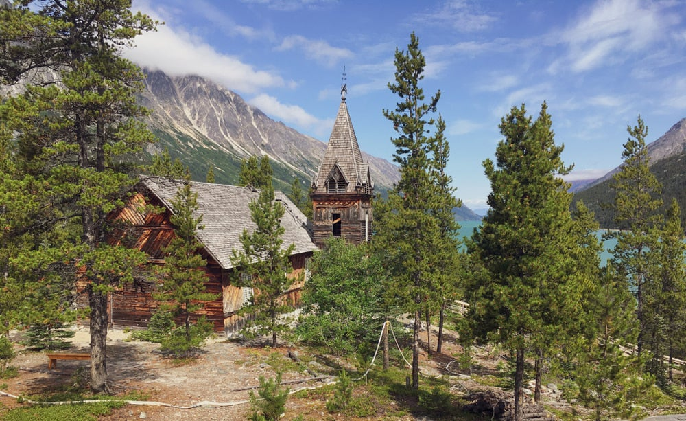 Old gothic style cabin with mountains and trees in background