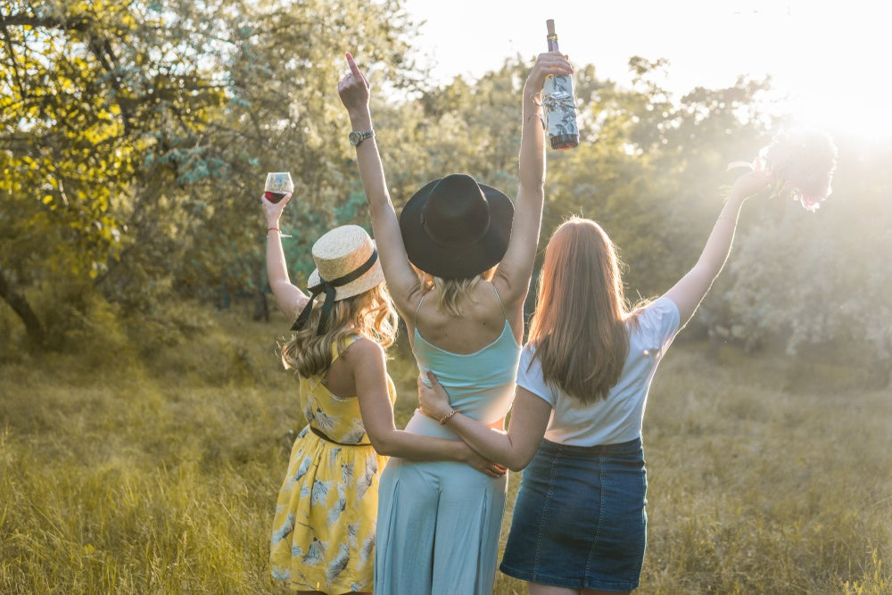 Three women holding drinks and flowers with trees surrounding them at a camping bachelorette party