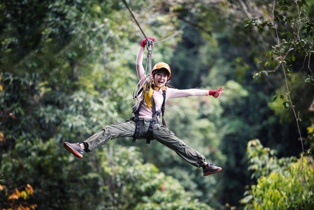Woman zip lining and smiling with trees surrounding her