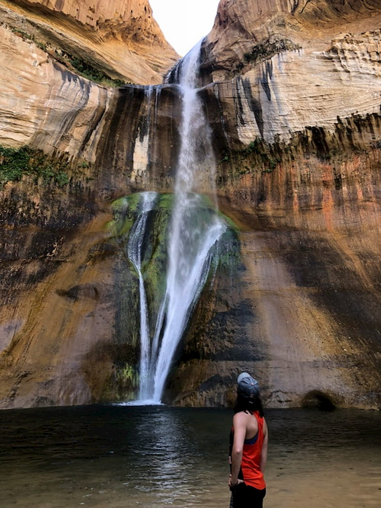 a woman stares at the bottom of a waterfall in utah