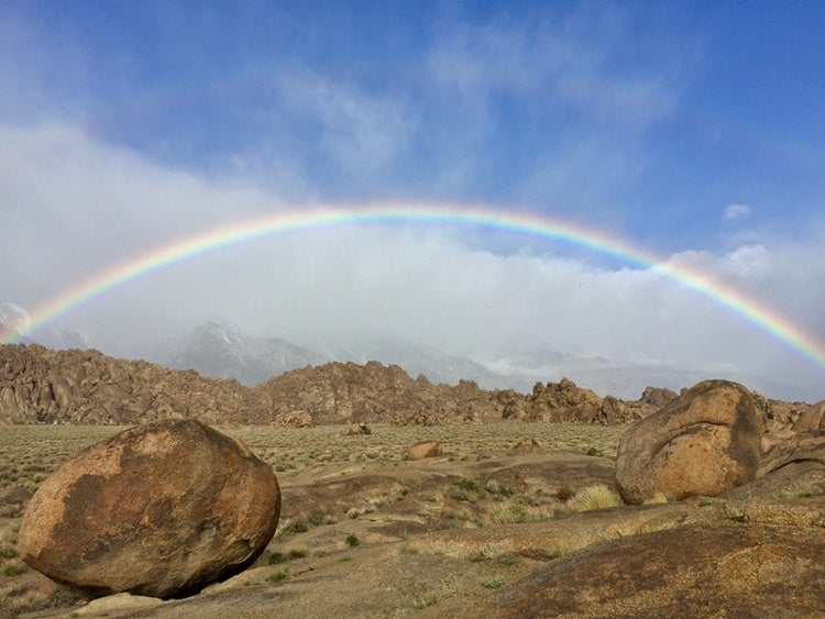 a rainbow stretches over rock carins in a desert in california