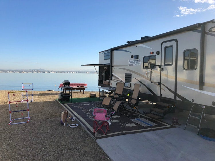 a parked RV with a rug, chairs, bathroom and games set up on a campground near a lake