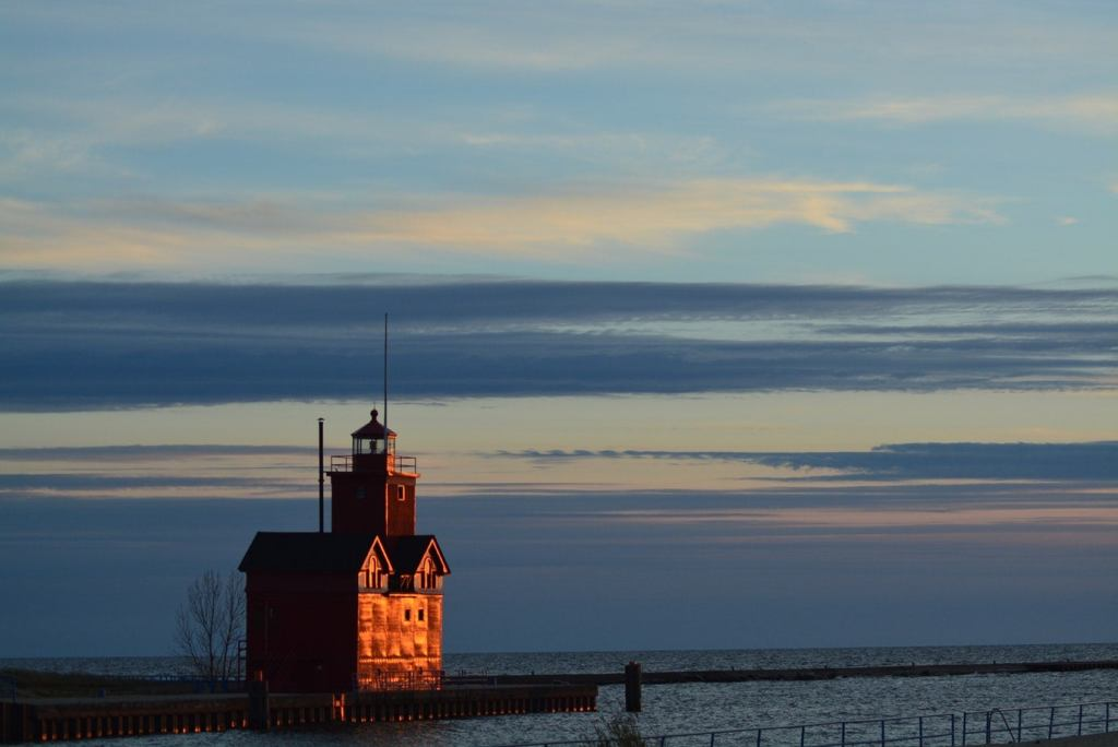 a stocky red lighthouse on a pier into lake michigan