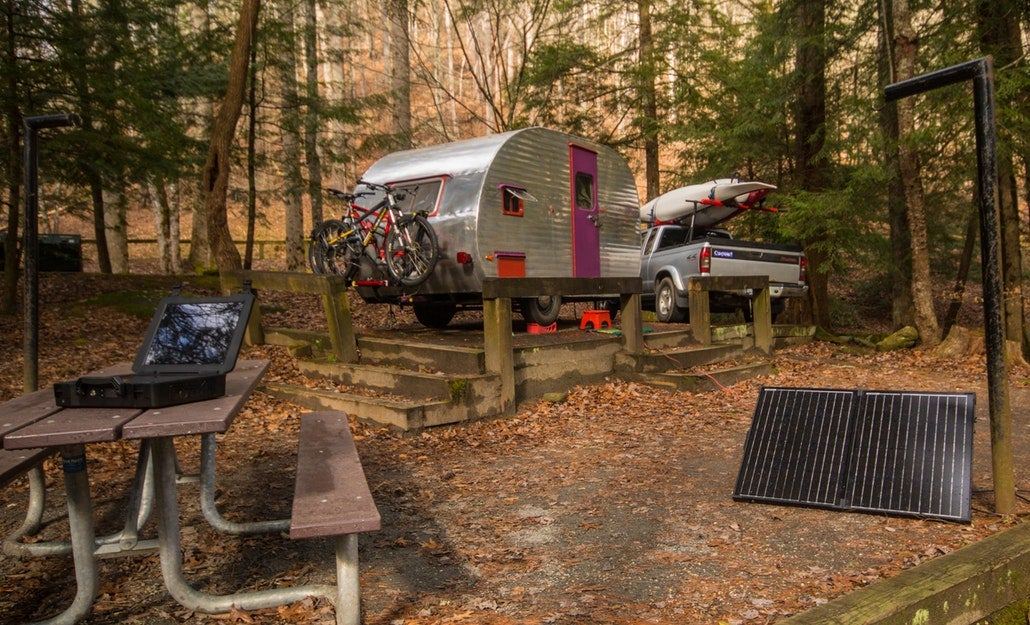 a campsite with a car and campervan, a portable charger on a picnic table and a solar camping generator