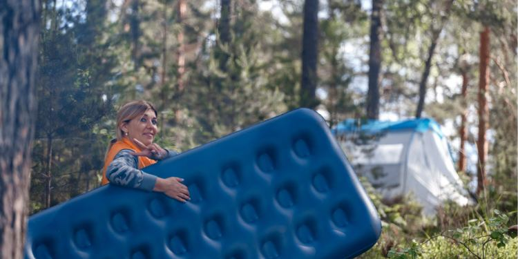 a woman smiling holding a camping air mattress at a campground